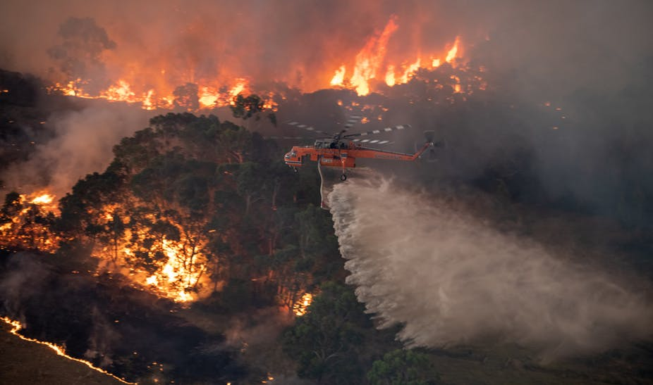 A firefighting helicopter tackles a bushfire near Bairnsdale in Victoria's East Gippsland region, Australia.